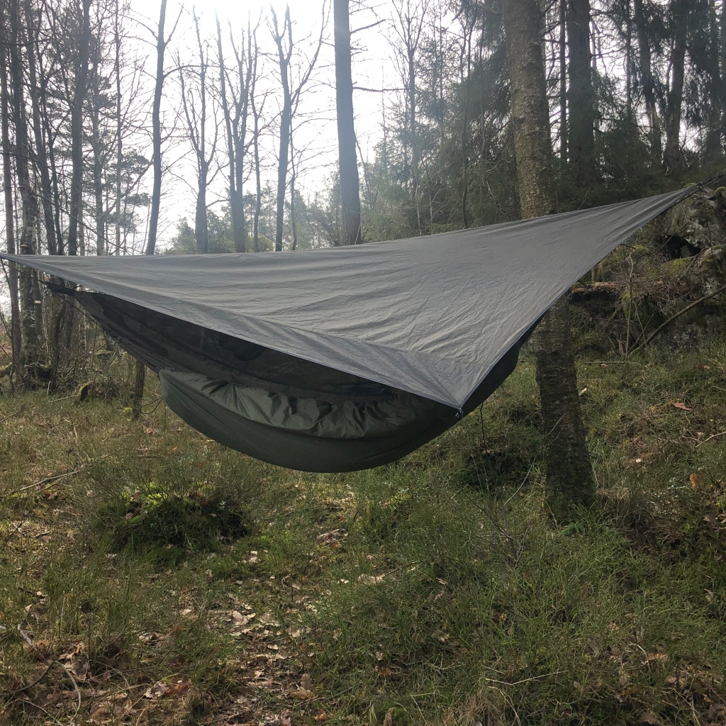 A hennessy hammock is pitchen between two trees. It has a rainfly covering it. Under rests a DD banket made from a material that reminds of a sleeping bag. Everything is green.
